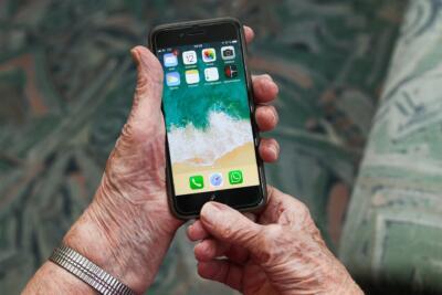 mains d'une dame agée tenant un telephone portable tactile